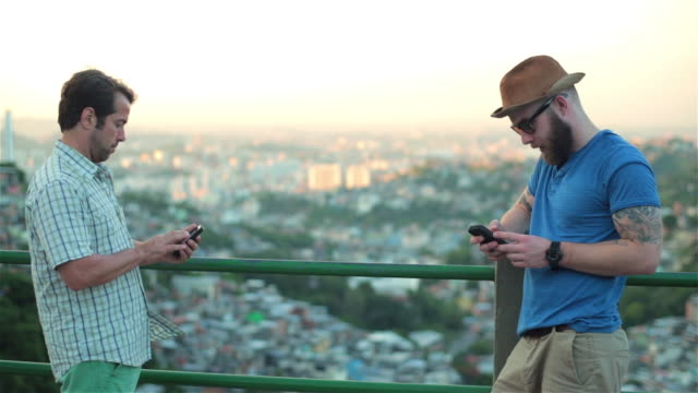 Two distracted men text on smartphones at scenic overlook of Rio de Janeiro