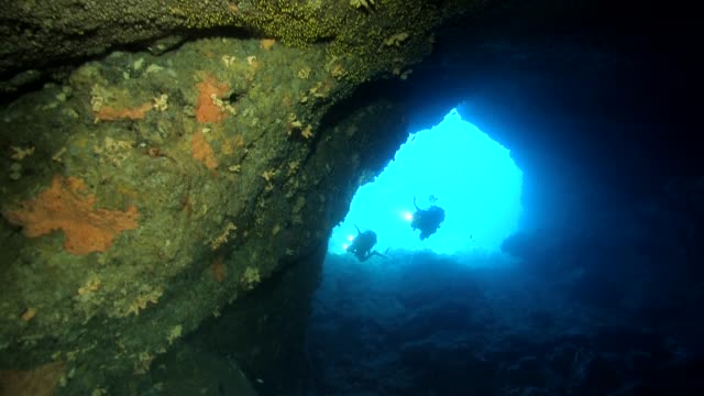 Two divers coming inside a cave with light