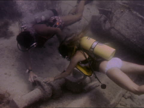 Two divers investigate a sunken ship
