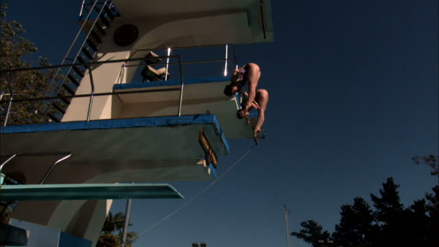 two divers jump from a diving board into a swimming pool. - 生理学点の映像素材/bロール