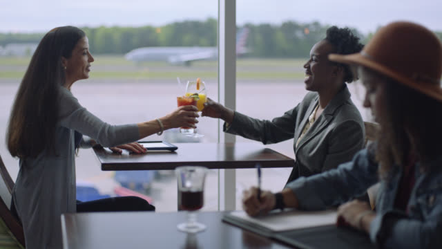stockvideo's en b-roll-footage met two diverse businesswomen cheers while they wait by a window at airport terminal cafe. - koffie drank