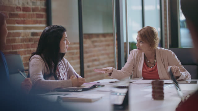 two diverse businesswomen exchange ideas and take notes during a team meeting - strategy stock videos & royalty-free footage