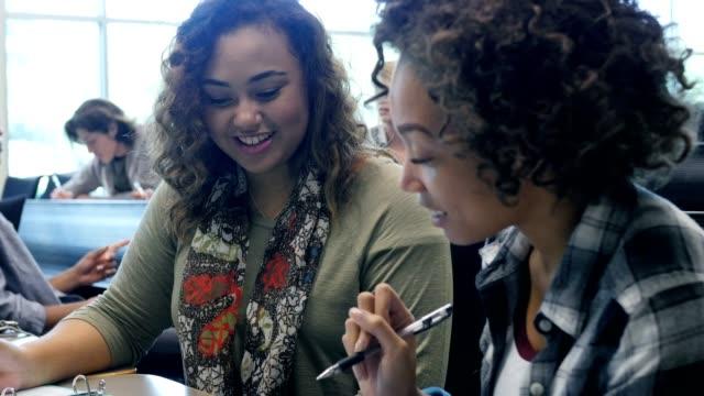 Dos diversas mujeres estudiantes estudian juntos en la clase