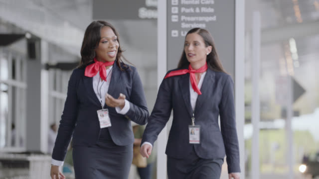 two diverse female flight attendants walk and talk outside airport at ground transportation. - crew stock videos & royalty-free footage