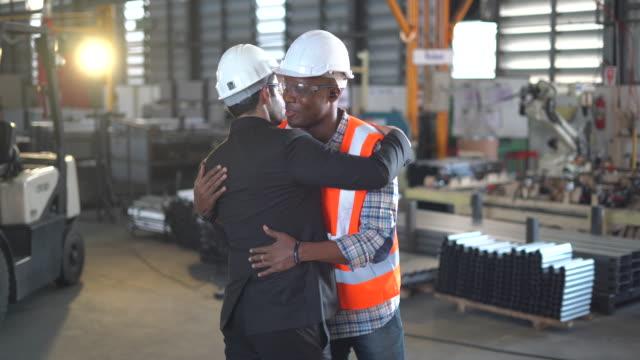vidéos et rushes de two diverse technology engineers discussing developing of new project at industrial site - santé et sécurité au travail