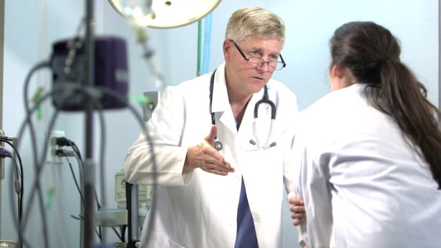 two doctors conversing in medical exam room - medical examination room stock videos & royalty-free footage