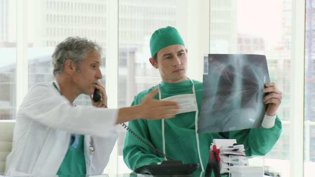 ms pan two doctors discussing chest x-ray and talking on phone / cape town, western cape, south africa - chirurgenkappe stock-videos und b-roll-filmmaterial