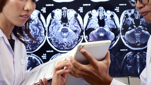 vídeos de stock, filmes e b-roll de dois médicos discutindo ressonâncias em digital tablet pc - cirurgião