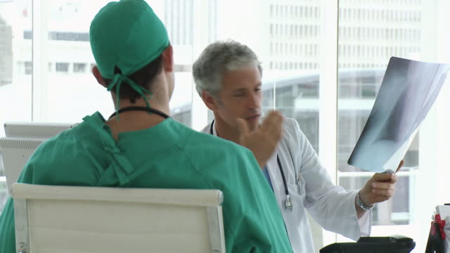ms two doctors discussing x-ray / cape town, western cape, south africa - operating gown stock videos & royalty-free footage