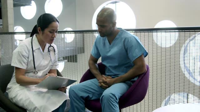 vídeos de stock, filmes e b-roll de two doctors in consultation - mãos juntas