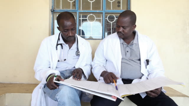 Two doctors look at notes together at a clinic in Kenya.