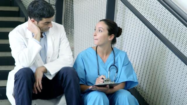 vídeos de stock e filmes b-roll de two doctors on staircase - bata cirúrgica