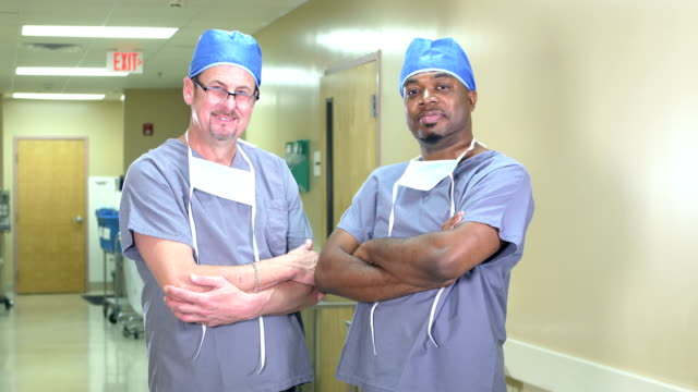 two doctors or surgeons in hospital corridor - surgeon stock videos & royalty-free footage