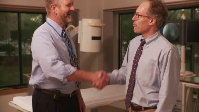 stockvideo's en b-roll-footage met ms two doctors shaking hands and talking / south burlington, vermont, usa - onderzoekstafel