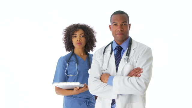 two doctors standing looking at camera - untersuchungskittel stock-videos und b-roll-filmmaterial