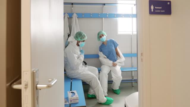 zwei ärzte nehmen schutzausrüstung in der umkleidekabine des krankenhauses ab - medizinerkleidung stock-videos und b-roll-filmmaterial