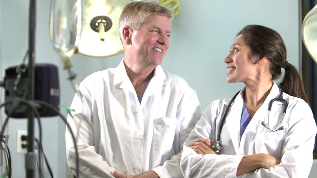two doctors talking, smiling, looking at camera - pacific islander doctor stock videos & royalty-free footage