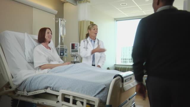 stockvideo's en b-roll-footage met ws two doctors talking to female patient sitting in hospital bed, seattle, washington, usa - man met een groep vrouwen