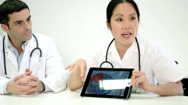 Two doctors using digital tablet
