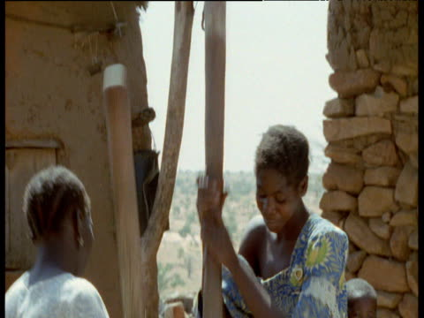 stockvideo's en b-roll-footage met two dogon women pound millet, chickens peck around base of container, mali - cereal plant