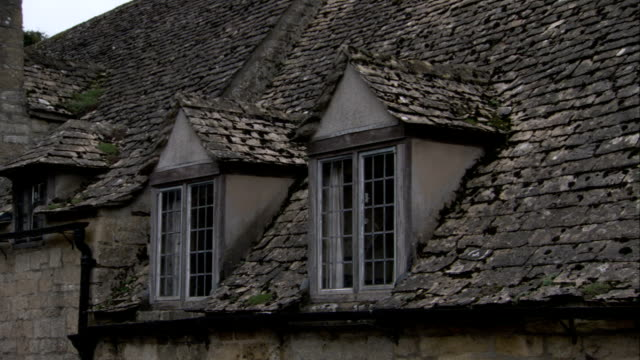 vídeos y material grabado en eventos de stock de two dormer windows line the slate roof of a stone building in lower slaughter, england. available in hd. - pizarra roca metamórfica