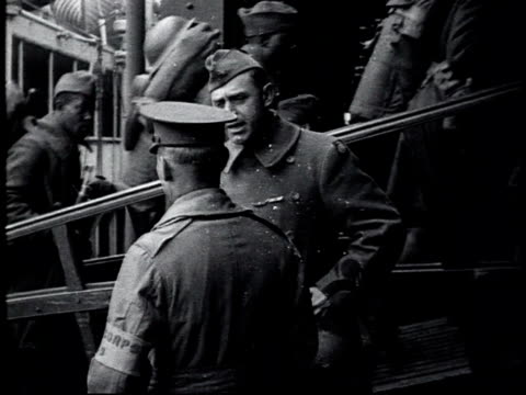 vídeos y material grabado en eventos de stock de two doughboys talking as a line of soldiers is boarding a ship behind them / united states - 1910 1919