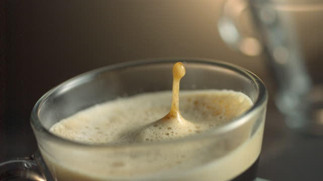 Two drops of coffee splash into frothy cream and coffee in a coffee cup.