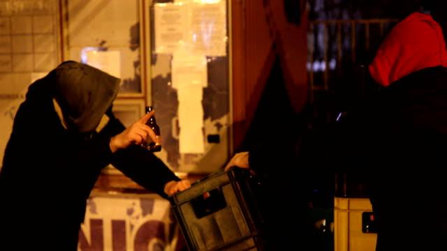 Dos hombres borrachos con cerveza al aire libre en la noche de frío invierno