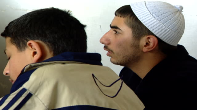of two druze schoolboys in a class at the irfan religious school, one of them is wearing a white beanie aka allouseh, which is traditional druze... - theology stock videos & royalty-free footage