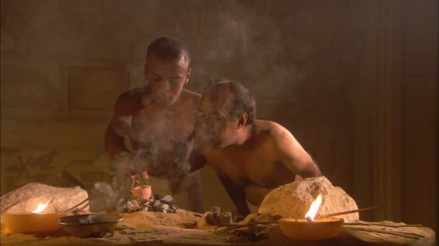 two dwarf men in ancient egypt smelt ore in a clay pot over a fire. - historische nachstellung stock-videos und b-roll-filmmaterial