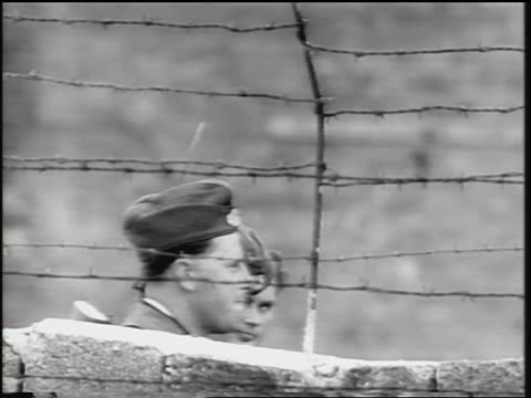 pan two east german soldiers walking behind berlin wall / cold war - 1961 stock videos & royalty-free footage