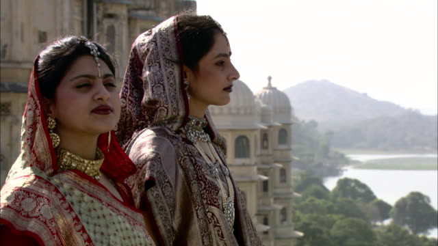 two east indian women stand on a wall overlooking lake pichola. - hinduism stock videos & royalty-free footage