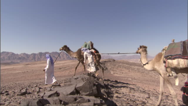 two egyptians in native dress walk in the desert leading saddled camels. - 頭飾り点の映像素材/bロール