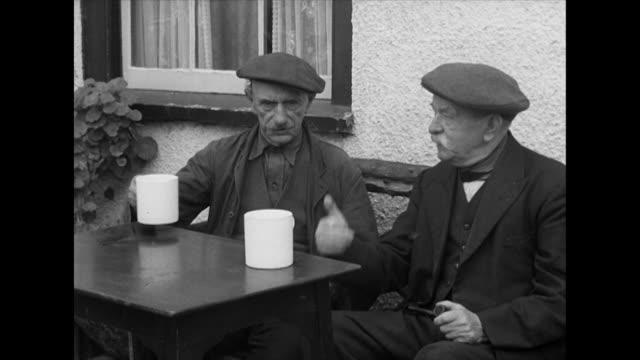 Two elderly men enjoying a pint of cider