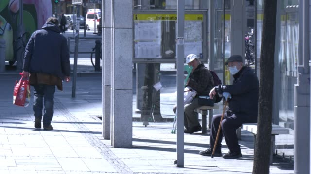 two elderly men wearing a protective face mask wait for the public bus at bahnhof zoo district during the coronavirus crisis on april 9, 2020 in... - social issues video stock e b–roll