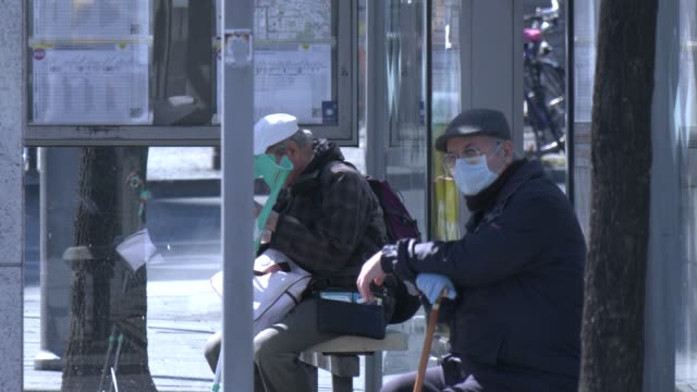 two elderly men wearing a protective face mask wait for the public bus at bahnhof zoo district during the coronavirus crisis on april 9 2020 in... - öffentliches verkehrsmittel stock-videos und b-roll-filmmaterial