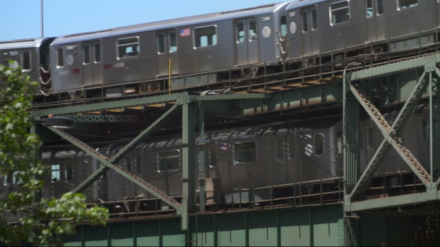 two elevated subway 7 trains pass each other on a railroad bridge in long island city in new york. - hochbahn passagierzug stock-videos und b-roll-filmmaterial