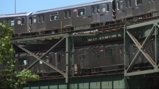 two elevated subway 7 trains pass each other on a railroad bridge in long island city in new york. - long island railroad stock videos and b-roll footage