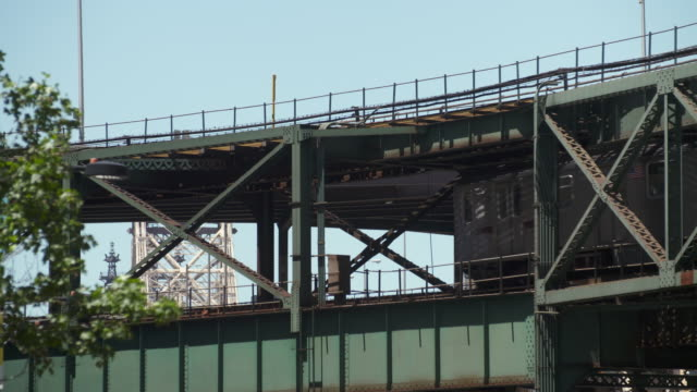 two elevated subway 7 trains pass each other on a railroad bridge in long island city in new york. - long island railroad stock videos & royalty-free footage