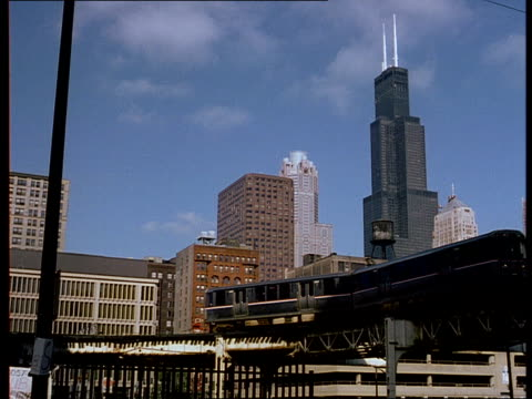 Two elevated trains pass each other near downtown Chicago.
