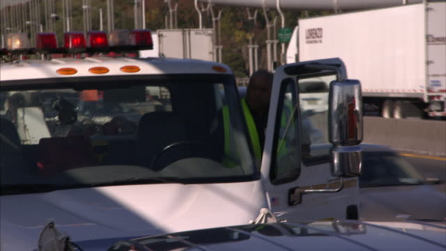 two employees get back into a tow truck on a busy freeway. - tow truck stock videos and b-roll footage