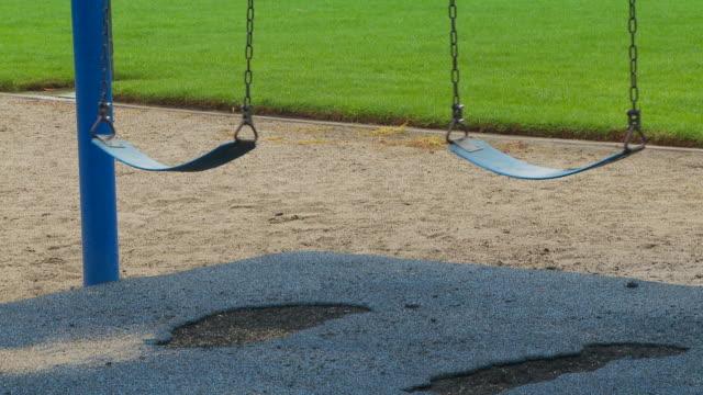 vídeos de stock e filmes b-roll de two empty swings rocking in the breeze - equipamento de parque infantil