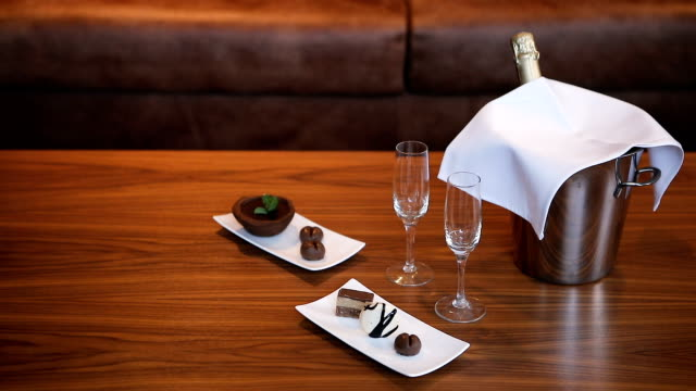 vídeos de stock e filmes b-roll de two empty wineglasses, champagne bottle and cookies on the table - sala de casa
