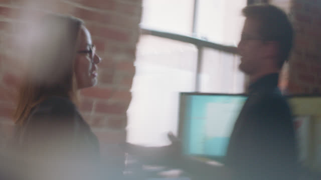 two energetic business colleagues have a conversation in the office - defocussed stock videos & royalty-free footage