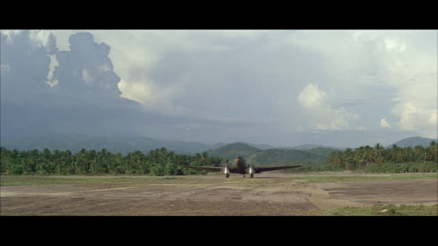 vídeos de stock, filmes e b-roll de ms two engine airplane taxis landing in length of crude landing strip in tropics - formato letterbox