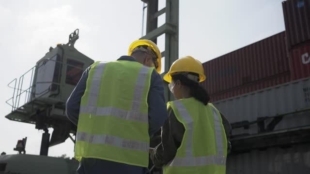 貨物コンテナの前に輸送貨物貨物をチェック安全ヘルメットを持つ2人のエンジニアの男性. - 造船所点の映像素材/bロール