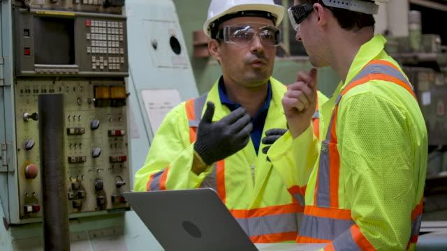 vídeos de stock, filmes e b-roll de dois engenheiros trabalhando na fábrica. - operário de linha de produção