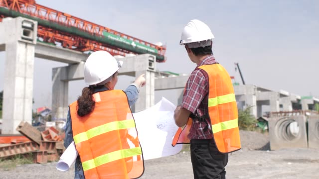 two engineers discussing and talking on blueprint at construction site - caposquadra video stock e b–roll