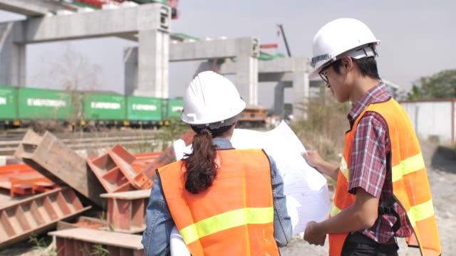 建設現場の青写真について話し合う2人のエンジニア - 工事点の映像素材/bロール