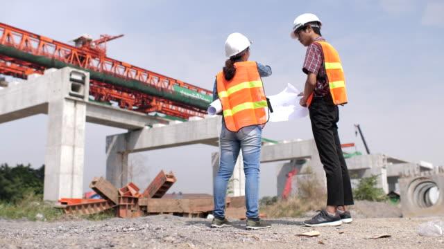 工事現場で設計図を議論する 2 つのエンジニア - スポーツヘルメット点の映像素材/bロール